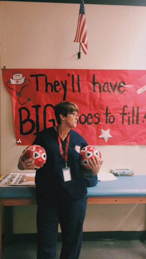 Nurse Scully in her office on her last day at LRHS holding soccer balls given to her by the girls she has coached.